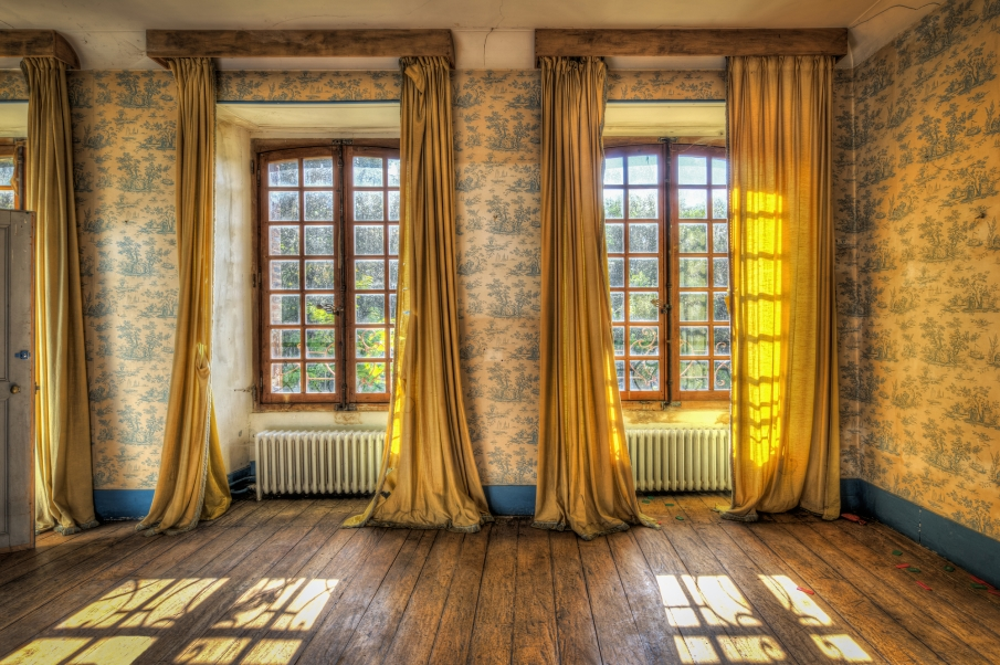 Windows with yellow curtains in an abandoned castle
