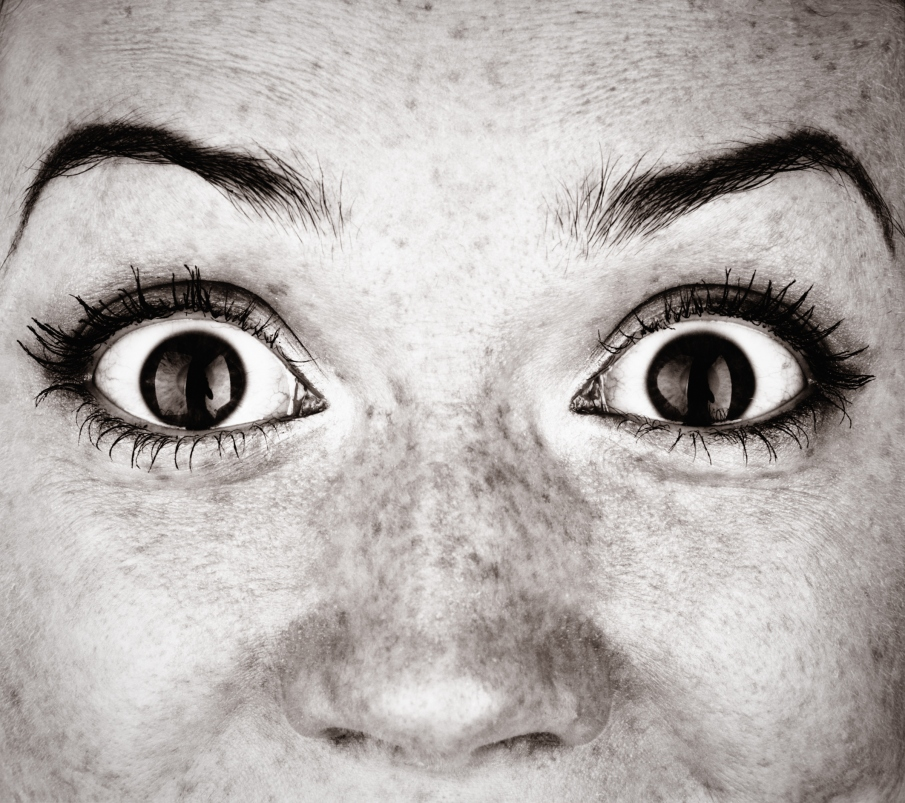 Close-up of woman's bulging eyes in black and white